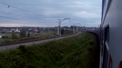 Trans-Siberian Railway train in a sharp curve while passing by a village Stock Footage
