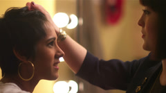 Female model getting her hair touched-up by another female Stock Footage