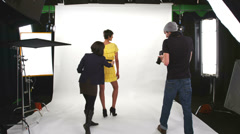 Behind the scenes of a female model being photographed by a male photographer Stock Footage