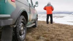 Traveller standing near the SUV on snowy mountain plateau Stock Footage