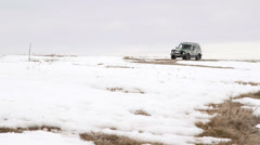 Off-road vehicle riding through the snowy Crimean plateau Stock Footage