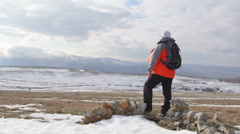 Man hiker with outstretched arms on snowy mountain plateau Stock Footage