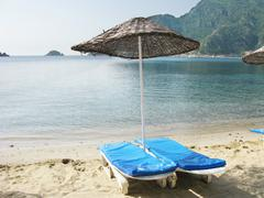 beach with sun-tents and sun-beds - stock photo