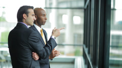Two male Business Professionals Work Together, while looking out a window Stock Footage