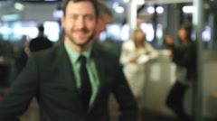 An attractive young businessman works alone and then smiles at the camera. - stock footage