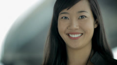 A young businesswoman with a tablet smiles at the camera, then joins a meeting. - stock footage