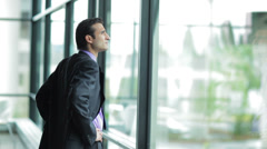 A young businessman walks up to a window and looks out - stock footage