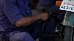 Indian mechanic sticks rubber on bike wheel and replaces it Stock Footage