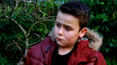 Depressed boy, background trees in the wind Stock Footage