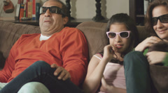 Stock Video Footage of Family of four watching a movie at home on a couch wearing 3D glasses
