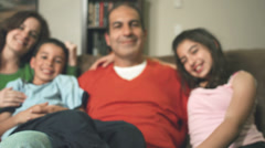 A family of four sit on a couch and they all smile at the camera Stock Footage