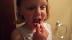 An adorable little girl feels her loose tooth. Stock Footage
