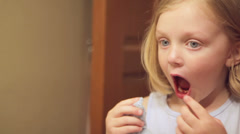 A cute little girl looks in the mirror at the spot her tooth used to be. Stock Footage