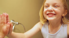 A proud adorable little girl looks at her teeth in the mirror. Stock Footage