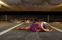 Young Woman holding yoga poses in a public space Stock Photos