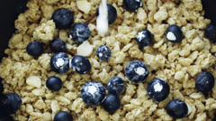 CU HA Studio shot of milk being poured into muesli with blueberries - stock footage