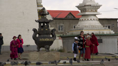 Pan from monks walking in front of the Gandan Monastery in Ulaan Bataar Stock Footage