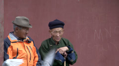 Two elderly man sitting on a bench at the Gandan Monastery Stock Footage