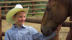 A boy in a cowboy hat stands in front of a horse with grass in his mouth - stock footage