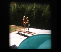 Young brother and sister jump off diving board Stock Footage