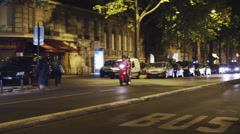 WS PAN Night street scene with couple on moped / Paris, France - stock footage