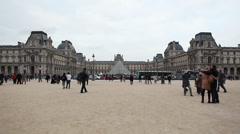 Tourists walk on a background Louvre in Paris Stock Footage
