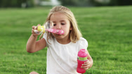 Stock Video Footage of MS Girl (4-5) playing with bubble wand in park / Orem, Utah, USA