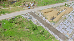 Aerial flight over mass graves with body bags after typhoon Haiyan Stock Footage
