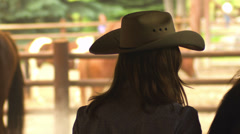 A young cowgirl with a hat brushing a horse in a pen - stock footage