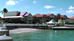 Cayman Islands, buildings in the shore street with a small beach in foreground Stock Footage