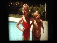 Cute blond boy and girl pose for camera poolside Stock Footage