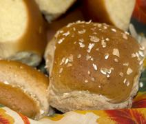 One Wheat Roll Among Many Dinner Rolls in a Basket - stock photo
