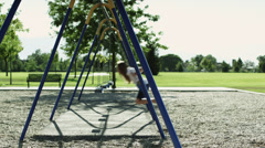 WS PAN Girl (10-11) on swing in park / Orem, Utah, USA Stock Footage
