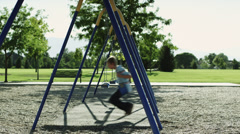 WS PAN Boy (12-13) on swing in park / Orem, Utah, USA - stock footage
