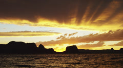 SLO MO WS Silhouette of man jumping to Lake Powell at sunset / Utah, USA Stock Footage