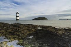 penmon beach, anglesey, wales. lighthouse and puffin island. - stock photo