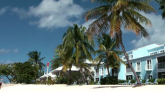 Cayman Islands, villas and palm trees at seven mile beach, pan to the sand Stock Footage