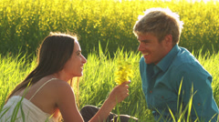 A cute young couple in love sit in grass in an open field with yellow flowers - stock footage