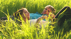 A cute young couple in love lay in grass in an open field with yellow flowers - stock footage