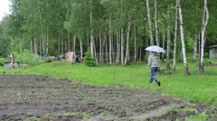 Farmer woman in gumboots with umbrella walk near birch trees Stock Footage