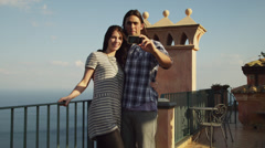 MS Couple taking self portrait with mobile phone, standing by balustrade on Stock Footage