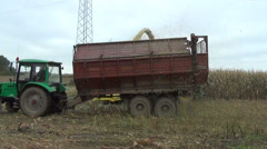 Maize field works harvester cut pour grain into tractor trailer Stock Footage