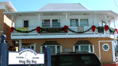 Cayman Islands, sign of hog sty bay and a building with bay windows and balcony Stock Footage