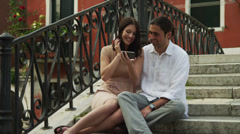 MS Young couple sitting on bridge and looking at mobile phone / Venice,Italy Stock Footage