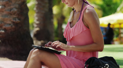 MS TU Woman typing on tablet pc in park / South Beach, Miami, Florida, USA Stock Footage