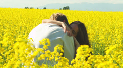 Stock Video Footage of A young couple in love laugh and kiss in a open field with yellow flowers