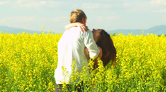 Stock Video Footage of A young couple in love dance and hug in a open field with yellow flowers