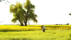 Stock Video Footage of Wide shot of a young couple in love holding hands in a field with yellow flowers