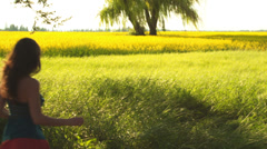 A young couple in love running in a open field with yellow flowers Stock Footage