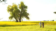 A young couple in love hug and spin around in a open field with yellow flowers - stock footage